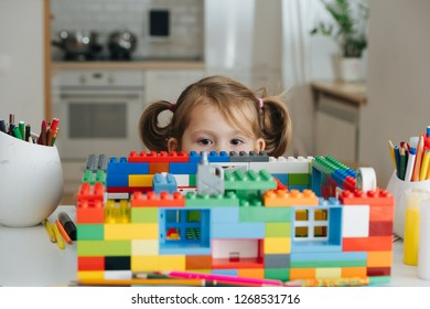 Little girl with two tails playing with doll house constructor at home. She is looking out from behind the toy. Upper half of the face. Looking at camera.