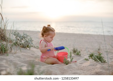 A little girl with two tails in a striped bodysuit plays on a sandy beach with a shovel and a bucket in the rays of the setting sun.