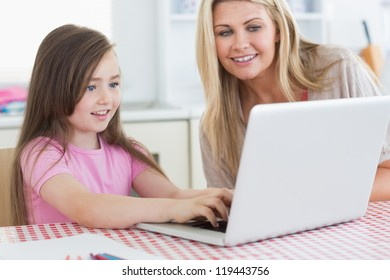 Little girl typing on laptop with her mother next to her in the kitchen