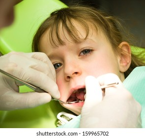Little girl under prophylaxy dental examination