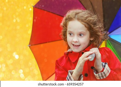 Little girl  under an umbrella from the rain. Happy childhood concept.