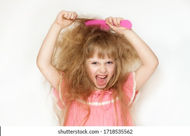 a little girl with unruly, tangled long hair in a pink dress on a white background tries to comb it