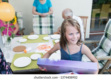 The little girl unwraps a birthday present during a garden party with her sisters and family - authentic family life