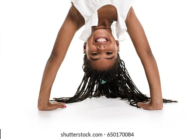 A little girl upside down on a white background
