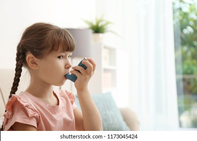 Little girl using asthma inhaler on blurred background