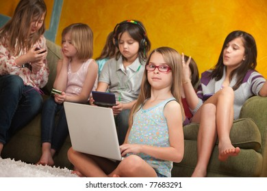 Little girl using laptop while her friends are busy playing on video game consoles