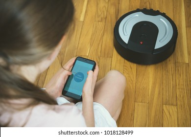 Little girl using mobile app to control robotic vacuum cleaner.