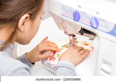 Little girl using sewing machine to make crafts