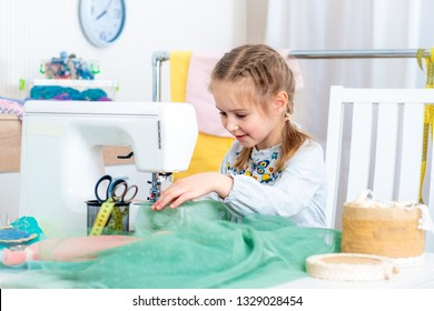 Little girl using sewing machine to make crafts in the workshop