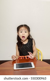 Little girl using tablet computer sitting at table.