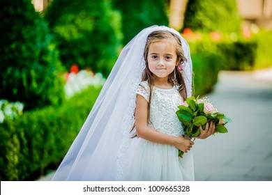 Ein kleines Mädchen in einem Schleier und mit einem Bouquet sieht wie eine Braut aus