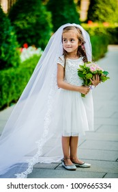 A little girl in a veil and with a bouquet looks like a bride
