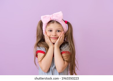 The little girl is very happy and holds her hands near her cheeks.