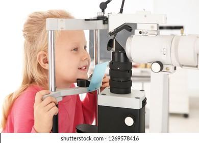 Little girl visiting children's doctor in clinic. Eye examination