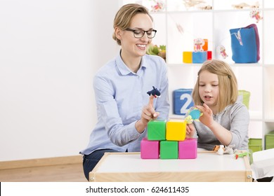 Little girl visiting psychologist and playing with toys