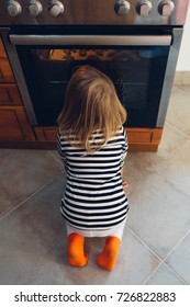 Little girl waiting for the cakes in front of the oven