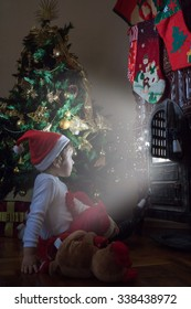 Little girl waiting Santa Claus by the fireplace