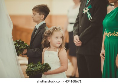 little girl waiting for young couple in church
