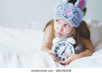 Little girl wakes up in morning under white blanket wearing grey bunny plush sleep mask with alarm clock in her mouth. Child sleep regime hours. Early rise to kindergarten. Mom's daily rest routine.