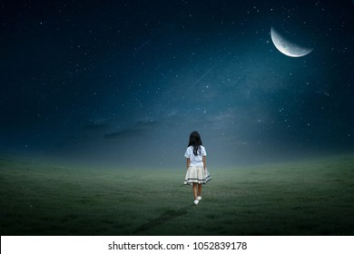 The little girl walked in the lawn in half-lonely half moon.