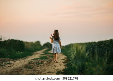 Little girl walking alone on a dusty road in the sunset.