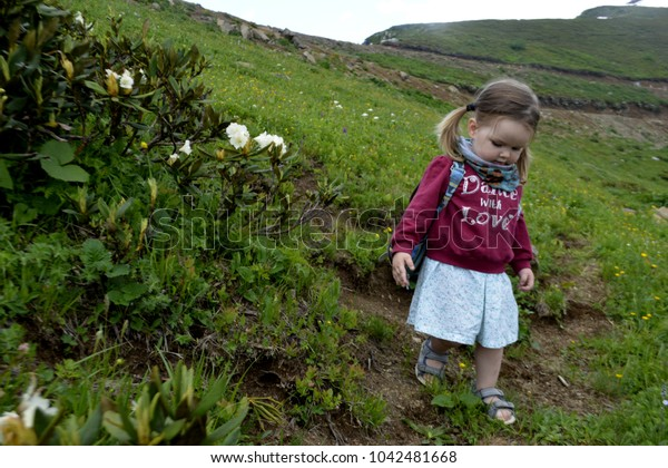 Little girl walking along the path in the mountains