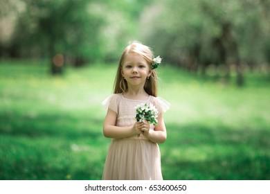 Little girl is walking in an apple garden