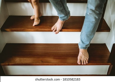 a little girl walking down the stairs hand in hand with her fath