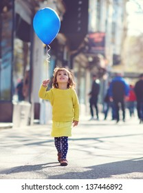 Little Girl walking down the street with a blue balloon