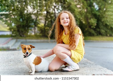 Little girl walking with her puppy jack russell.