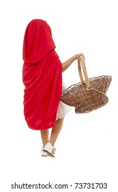 little girl walking holding a basket using a red cape