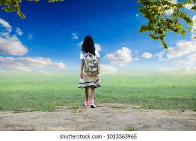Little girl walking the lawn in the park on a bright sunny day.