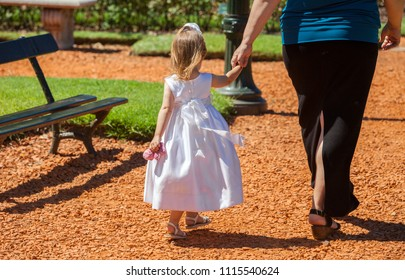 little girl walking with mom in the park