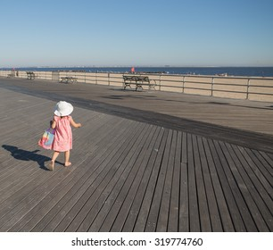 Little girl walking on the boardwalk in a sunny day. Photographed in Coney Island, Brooklyn, NY, USA in September 2015.