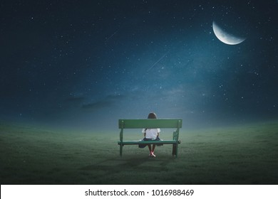 The little girl was walking on a chair in the lawn at night under the moonlight on a beautiful half-moon night.