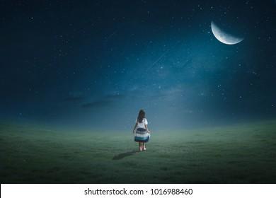 Little girl walking on the lawn in the moonlight half moon beautifully.