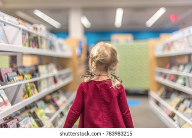 Little girl walking through the children's section at the library choosing books