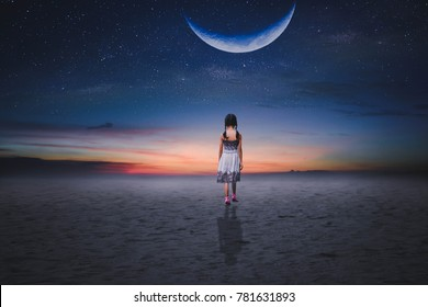 A little girl walks along the desert before dawn, in the half moon, it disappears beautifully.