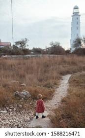 A little girl walks along the path to the lighthouse, a walk near the autumn sea