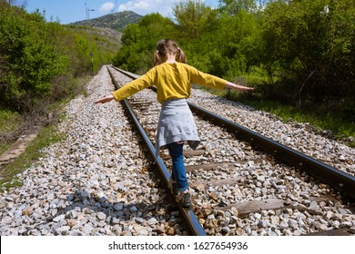 Little girl walks balance on railway track with arms spread. Shot from back, no face, bright sunny day in nature.