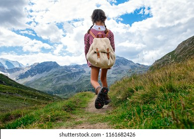 Little girl walks on mountain trail during an excursion. with the backpack.