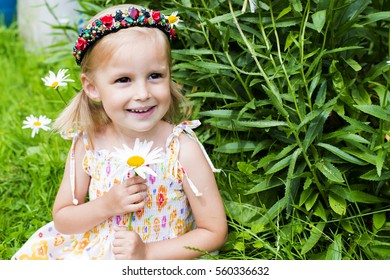 The little girl walks in summer day, smiles