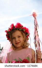 A little girl with a wand dressed up like a fairytale princess.