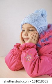 Little girl in warm coat with hat, on gray background.