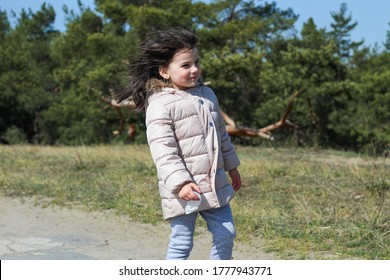 A little girl in a warm long jacket walks along an asphalt road towards the wind in a park
