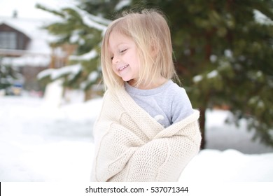 little girl in a warm scarf walks in the winter garden