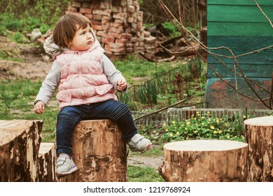 A little girl in a warm waistcoat and jeans sits on a stump in the village, ecotourism, holidays with her grandmother