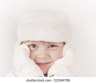 little girl in warm white hat and  mittens
