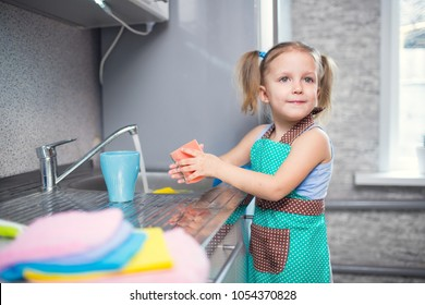 little girl washes dishes at home in the kitchen in the sink
