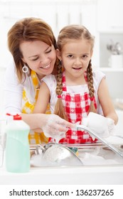 Little girl washing dishes helped by her mother - closeup